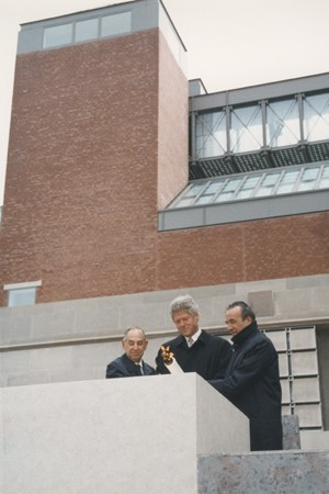 "<p>President Bill Clinton (center), <a href=""/narrative/10130"">Elie Wiesel</a> (right), and Harvey Meyerhoff (left) light the eternal flame outside on the Eisenhower Plaza during the dedication ceremony of the <a href=""/narrative/7511"">United States Holocaust Memorial Museum</a>. April 22, 1993.</p>"