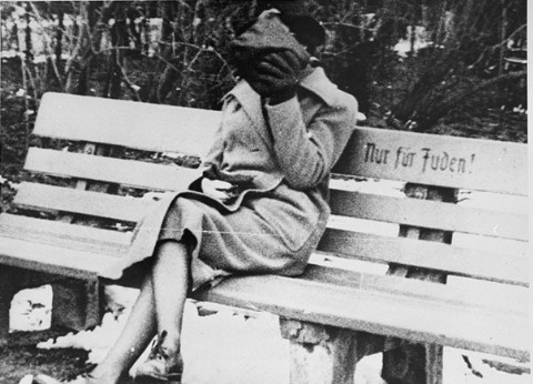 "A woman who is concealing her face sits on a park bench marked ""Only for Jews."" [LCID: 11195]"