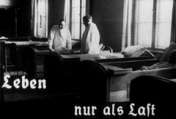 "<p>This photo originates from a film produced by the Reich <a href=""/narrative/11806"">Propaganda Ministry</a>. It shows two doctors in a ward in an unidentified asylum. The existence of the patients in the ward is described as ""life only as a burden."" Such <a href=""/narrative/81"">propaganda</a> images were intended to develop public sympathy for the <a href=""/narrative/4032"">Euthanasia Program</a>.</p>"