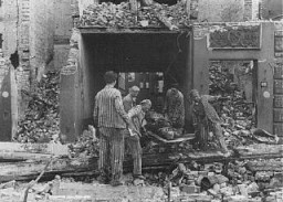 <p>Concentration camp prisoners, many from satellite camps of Neuengamme, remove corpses of German civilians after Allied bombings of Hamburg. Germany, August 1943.</p>