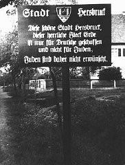 "<p>在巴伐利亚北部的一个城镇外面,一块指示牌警告道:""赫斯布鲁克 (Hersbruck) 城,这可爱的赫斯布鲁克城、这地球上的显赫之地,仅为德国人而非犹太人建造。因此,此处不欢迎犹太人。""拍摄地点:德国,赫斯布鲁克,拍摄时间:1935 年 5 月 4 日。</p>"