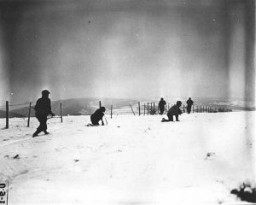 <p>John Perry, a movie photographer with Unit 129, films GIs of the 290th Infantry Regiment, 75th Infantry Division, and 4th Cavalry Group ferreting out German snipers near Beffe, Belgium. Twelve Germans were killed. The scene was photographed by Carmen Corrado of the 129th. January 7, 1945. US Army Signal Corps photograph taken by C.A. Corrado.</p>