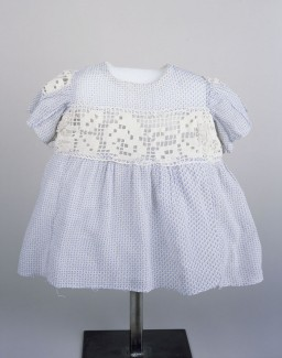 """<p>A blue and white child's dress worn by Sabina Kagan while living in hiding with the <a href=""""/narrative/59137/en"""">Roztropowicz family</a> in Radziwillow, <a href=""""/narrative/4879/en"""">Poland</a>, during <a href=""""/narrative/2388/en"""">World War II</a>. Her rescuers used doll's clothing to make this dress.</p> <p><span class=""""Text11VerdanaBlack"""">Sabina was just an <a href=""""/narrative/2562/en"""">infant</a> when <a href=""""/narrative/10800/en"""">SS</a> mobile killing squads began rounding up Jews in the Polish village of Radziwillow in 1942. Her parents persuaded a local policeman to hide the family. The policeman, however, soon asked the Kagans to leave but agreed to hide baby Sabina. Her parents were captured and <a href=""""/narrative/6590/en"""">killed</a>. Sabina was concealed in a dark basement, with minimal food and clothing. She was discovered and taken in by the Roztropowicz family in 1943. Like most <a href=""""/narrative/7711/en"""">hidden children</a>, Sabina had few personal belongings. Her foster mother Natalia even made her some clothing from doll clothes. This blue and white dress with crochet inserts in the waist and sleeves is one of the few pieces of clothing Sabina had. It measures just 13 inches from neck to hemline.</span></p>"""