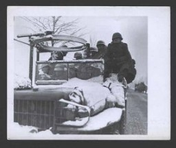 <p>Des GI montent au front dans des camions ouverts, par des températures négatives, en vue d'arrêter l'avancée des Allemands. 22 décembre 1944. Corps de transmission de l'Armée américaine, photo prise par J. Malan Heslop.</p>