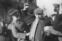 "<p>German personnel on Grzybowska Street arrest and search Jewish men who supposedly hid weapons prior to the German occupation of <a href=""/narrative/2014"">Warsaw</a>.  Warsaw, Poland, October-December 1939.</p>