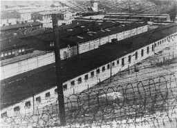 View, through the barbed wire, of the prisoner barracks in the Flossenbürg concentration camp. [LCID: 06012]