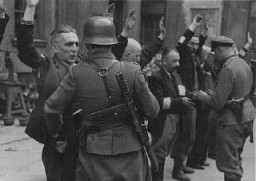 """<p>German soldiers arrest Jews during the <a href=""""/narrative/3636/en"""">Warsaw ghetto uprising</a>. Poland, May 1943.</p> <p>The Warsaw ghetto uprising began on April 19, 1943, after German troops and police entered the ghetto to deport its surviving inhabitants. By May 16, 1943, the Germans had crushed the uprising, deported surviving ghetto residents, and left the ghetto area in ruins.</p>"""