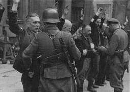 <p>جنود ألمان يلقون القبض على يهود أثناء ثورة الحي اليهودي في فارصوفيا. بولندا، أيار/مايو 1943.</p>