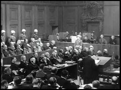 "<p>US prosecutor Thomas Dodd introduces the film compilation ""Nazi Concentration Camps."" At the end of the courtroom scene shown here, the lights are dimmed for the screening. The footage, filmed as Allied troops liberated the concentration camps, was presented in the courtroom on November 29, 1945, and entered as evidence in the trial.</p>"