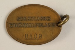 "<div class=""show-data"">Official identification tag (warrant badge) for the Criminal Police (Kriminalpolizei or Kripo), the detective police force of Nazi Germany. This side reads: Staatliche Kriminalpolizei (State Criminal Police) and identifies the officer's number as 8409.</div>