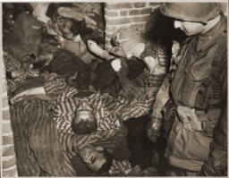 "<p>A US Army soldier views the bodies of prisoners piled on top of one another in the doorway of a barracks in <a href=""/narrative/7988/en"">Wöbbelin</a>. Germany, May 4–5, 1945.</p>"