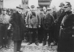 <p>Des Juifs arrêtés au cours de la Nuit de cristal (Kristallnacht) sont gardés avant d'être déportés vers le camp de concentration de Sachsenhausen. Zeven, Allemagne, 10 novembre 1938.</p>