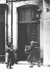 "<p>A Jewish woman carries her radio into a police station after a German order (August 8, 1941) demanded the confiscation of all radios owned by Jews. <a href=""/narrative/6033"">Paris</a>, France, 1941.</p>"