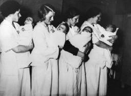 Des mères ayant accouché dans une maternité nationale-socialiste attendent que leurs enfants se fassent examiner par un docteur.