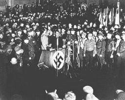 """<p>O Ministro da Propaganda Joseph Goebbels (no palanque) enaltecendo os estudantes e membros das <em>Sturm Abteilung</em>, Tropas de Choque nazistas, por seus esforços para destruir trabalhos considerados """"não-alemães"""", durante a noite de queima dos livros na Praça da Opera em Berlim, Alemanha. Dia 10 de maio de 1933.</p>"""