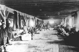 """<p>Judeus da Trácia e da Macedônia, então ocupadas pela Bulgária, confinados na fábrica de tabaco """"Monopol"""", a qual era utilizada como um campo de trânsito onde os prisioneiros eram alojados antes de serem enviados para o extermínio ou o trabalho escravo.  Posteriormente, foram todos deportados para o campo de extermínio de Treblinka.  Skopje, Macedônia.  Foto tirada entre 11-31 de março de 1943</p>"""