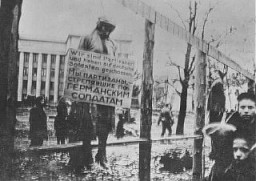 "<p>The public hanging of three members of the Communist underground on Karl Marx Street in <a href=""/narrative/3605/en"">Minsk</a>. One of the victims wears a large placard around his neck that reads ""We are partisans and have shot at German soldiers.""<br /><br />This execution was one of four carried out in Minsk on October 26, 1941, by German troops with the 707th Infantry Division. Altogether, 12 members of the Communist underground were publicly hanged in four groups of three near a yeast-making factory. This is believed to be the first public execution after the <a href=""/narrative/2972/en"">German invasion of the Soviet Union</a> and it included the hanging of Masha Bruskina, a young Jewish woman. In each of the four cases, the bodies were left to hang for several days to serve as a warning to would-be resisters.</p>"