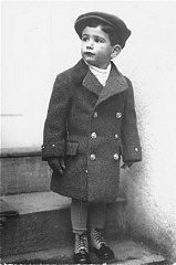 Three-year old Tomas Kulka stands in front of his house.