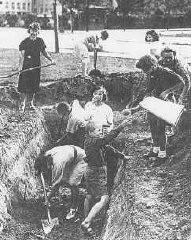 <p>A Varsavia, uomini, donne e bambini scavano trincee per la difesa durante l'assedio tedesco. Polonia, settembre 1939.</p>