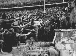 <p>يحي جمهور متحمس أدولف عند دخوله الملعب الأولمبي. برلين, ألمانيا, أغسطس 1936.</p>