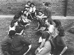 "<p>Jewish youth attend a class on transplanting seedlings, part of a general course in farming sponsored by the <a href=""/narrative/5002/en"">American Jewish Joint Distribution Committee</a> at the <a href=""/narrative/9359/en"">Bergen-Belsen displaced persons camp</a>. Germany, August 1, 1946.</p>"