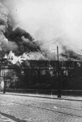 "<p>A building burns during the suppression of the <a href=""/narrative/3636/en"">Warsaw ghetto uprising</a>. The photograph was taken through the window of a building adjacent to the ghetto. Warsaw, Poland, May 1943.</p>"