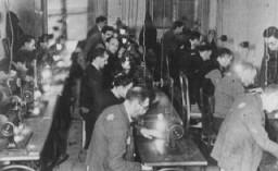 Habitants du ghetto, portant l'étoile jaune obligatoire, au travail forcé dans une usine textile.