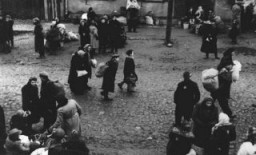 Jews carrying bundles of possessions before their deportation from the Kovno ghetto. [LCID: 10687]
