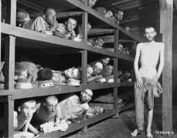 "<p>Former prisoners of the ""little camp"" in <a href=""/narrative/3963/en"">Buchenwald</a> stare out from the wooden bunks in which they slept three to a ""bed."" <a href=""/narrative/10130/en"">Elie Wiesel</a> is pictured in the second row of bunks, seventh from the left, next to the vertical beam. Abraham Hipler is pictured in the second row, fourth from the left. The man on the third bunk from the bottom, third from the left, is Ignacz (Isaac) Berkovicz. [He has also been identified as Abraham Baruch.] Michael Nikolas Gruner, originally from Hungary, is pictured on the bottom left corner. Perry Shulman from Klimitov, Poland is on the top bunk, second from the left (looking up). Buchenwald, Germany, April 16, 1945.</p>