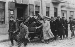 """<p>Jews deported from Prague, <a href=""""/narrative/7295/en"""">Czechoslovakia</a>, move their belongings through the streets of the <a href=""""/narrative/2152/en"""">Lodz</a> ghetto in occupied Poland. November 20, 1941.</p>"""
