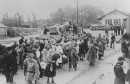 <p>زنان و کودکان و سالمندان یهودی در انتظار تبعید در ایستگاه راه آهن در کوسگ شهر کوچکی در شمال غربی مجارستان. کوسگ، مجارستان، ۱۹۴۴.</p>