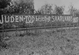 """<p>رسومات حائطية معادية للسامية مرسومة على حائط مقبرة يهودية تقول """"موت اليهود سينهي المحنة التي تمر بها ولاية سارلاند."""" برلين، ألمانيا، تشرين الثاني/نوفمبر من عام 1938.</p>"""