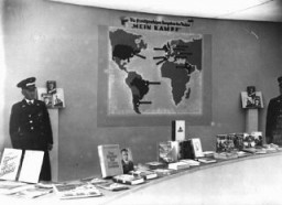 "<p>Exhibition of Nazi publications—carefully purged of antisemitic titles—on display during the Berlin <a href=""/narrative/7139"">Olympics</a>. The poster shows countries in which Hitler's <a href=""/narrative/11663""><em>Mein Kampf</em> </a>had been translated into the native language. Berlin, Germany, August 1936.</p>"