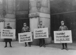 "<p>SA men in front of Jewish-owned store urge a <a href=""/narrative/102/en"">boycott</a> with the signs reading ""Germans! Defend Yourselves! Don't buy from Jews!"" Berlin, Germany, April 1, 1933.</p>"