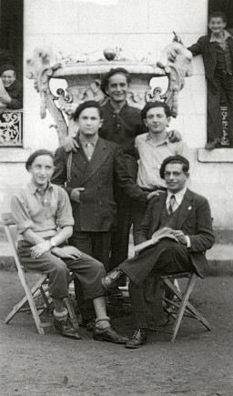 """<p>Group portrait at the <a href=""""/narrative/35442"""">Children's Aid Society</a> (<em>Oeuvre de Secours aux Enfants,</em>OSE) home for Orthodox Jewish children in Ambloy, France. Among those pictured: Kalman Kalikstein (front left), Binem Wrzonski (middle right), and <a href=""""/narrative/10130"""">Elie Wiesel</a> (back center). Photo dated 1945–1946.</p>"""