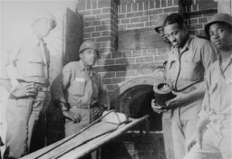 "<p>African American soldiers pose next to an oven in the crematorium of the Ebensee <a href=""/narrative/2689"">concentration camp</a>.</p>"