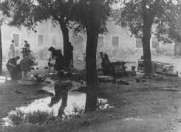 <p>تھیریسئن شٹٹ کی یہودی بستی میں عورتیں باہر کھانا پکارہی ہیں۔ تھیریسئن شٹٹ، چکوسلواکیا، 1941 اور 1945 کے درمیان۔</p>