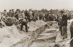 Mourners and local residents shovel dirt into the mass grave of the victims of the Kielce pogrom during the public burial. [LCID: 14390]
