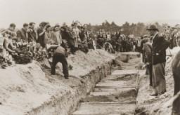 <p>Au cours de l'inhumation publique, les parents des défunts et les habitants des environs jettent de la terre dans la fosse commune des victimes du pogrom de Kielce.</p>