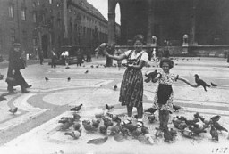 <p>Prewar family photograph of Berta and Inge Engelhard holding pigeons in a public square in Munich. Photograph taken in Munich, Germany, 1937.</p> <p>Following increased anti-Jewish measures, Berta and brother Theo (not pictured here) left Germany on a <em>Kindertransport</em> in January 1939. Inge followed on a different transport a few months later. While the siblings were eventually housed together in England, they faced many challenges during the war including the pain of separation from their parents.</p> <p>Parents Moshe and Rachel eventually escaped, and the family was ultimately reunited in England.</p>
