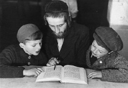 <p>Children learn a religious text from an Orthodox Jewish teacher. Landsberg displaced persons camp, Germany, 1946-1947.</p>