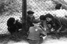 "<p>Family members say goodbye to a <a href=""/narrative/2562"">child</a> through a fence at the ghetto's central prison where children, the sick, and the elderly were held before deportation to Chelmno during the ""Gehsperre"" action. Lodz, Poland, September 1942.</p>"