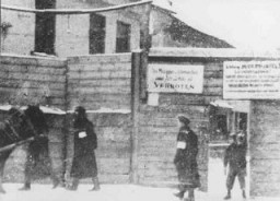 """<p>Thisphotograph shows the Rudnicki Street entrance to the <a href=""""/narrative/3169"""">Vilna</a> ghetto.The signs on the fence claim there is danger of contagion and prohibit the bringing of food or wood into the ghetto. Photograph taken in 1941–42.</p>"""