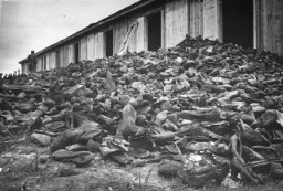 A Soviet soldier walks through a mound of victims' shoes piled outside a warehouse in Majdanek soon after the liberation. [LCID: 13108]