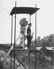 """<p>A British guard in a watchtower at Poppendorf displaced persons camp, after the arrival of Jewish refugees forced from the """"<a href=""""/narrative/5265/en"""">Exodus 1947</a>"""" refugee ship. Photograph taken by Henry Ries. Germany, September 1947.</p>"""