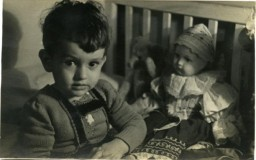 """<p>Benjamin Kedar (born Villiam Krausz) sits with a doll and a teddy bear shortly beforehis family went into hiding.</p> <p>Villiam'sparents married in Pragueand settled in Nitra, Slovakia. They worked as physicians. They had a daughter, Helen, in 1934, and Villiamin 1938. In 1942 the family relocated to a nearby village until September 1944. At that point, they went into hiding with Slovak peasants to avoid deportation to <a href=""""/narrative/3673/en"""">Auschwitz</a>.</p> <p>Villiam, his sister, and his parents survived the Holocaust. Other relatives were murdered: his grandfather died in Thersienstadt and his aunt in Auschwitz.</p>"""