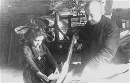 "<p>A Jewish man and child at <a href=""/narrative/3384/en"">forced labor</a> in a factory in the <a href=""/narrative/2152/en"">Lodz</a> ghetto. Lodz, Poland, date uncertain.</p>"