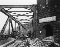 "<p>The sign erected by the <a href=""/narrative/7884/en"">9th Armored division</a> on the Ludendorff bridge after its capture. March 11, 1945. <a href=""/narrative/8129/en"">US Army Signal Corps</a> photograph taken by W. Spangle.</p>"
