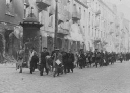"<p>Jews rounded up during the <a href=""/narrative/3636/en"">Warsaw ghetto uprising</a> are forced to march to the assembly point for deportation. Warsaw, Poland, April or May 1943.</p>"