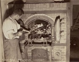 "<p>A survivor stokes smoldering human remains in a crematorium oven that was still lit in the <a href=""/narrative/4391"">Dachau</a> camp. Photograph taken upon the <a href=""/narrative/2317"">liberation</a> of the camp. Dachau, Germany, April 29-May 1, 1945.</p>"